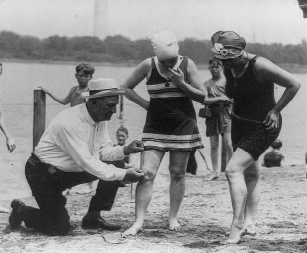 "In 1922, Bill Norton, the bathing beach ""cop"", is using a tape measure to determine the distance between a woman's knee and the bottom of her bathing suit"